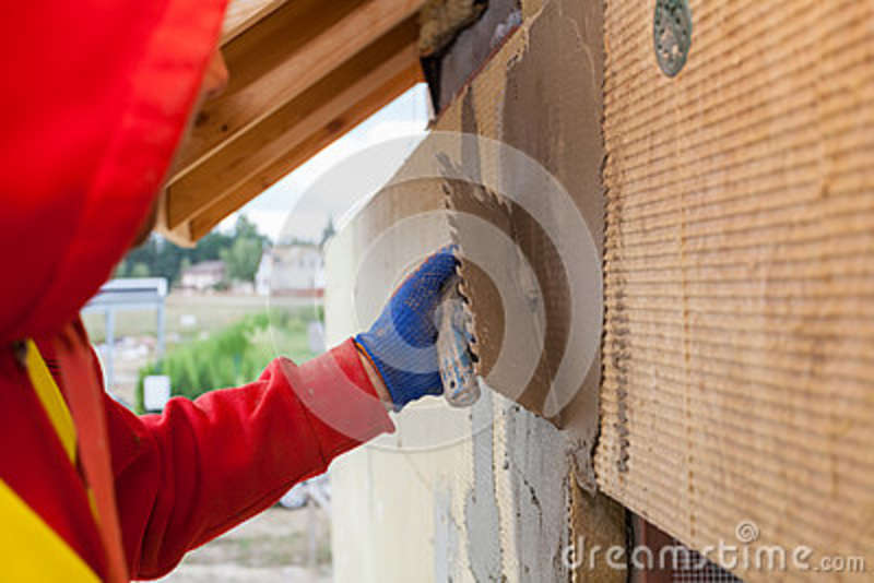 Worker plastering a facade of a new house on mineral rockwool panels. Process of insulation house for better energy efficiency