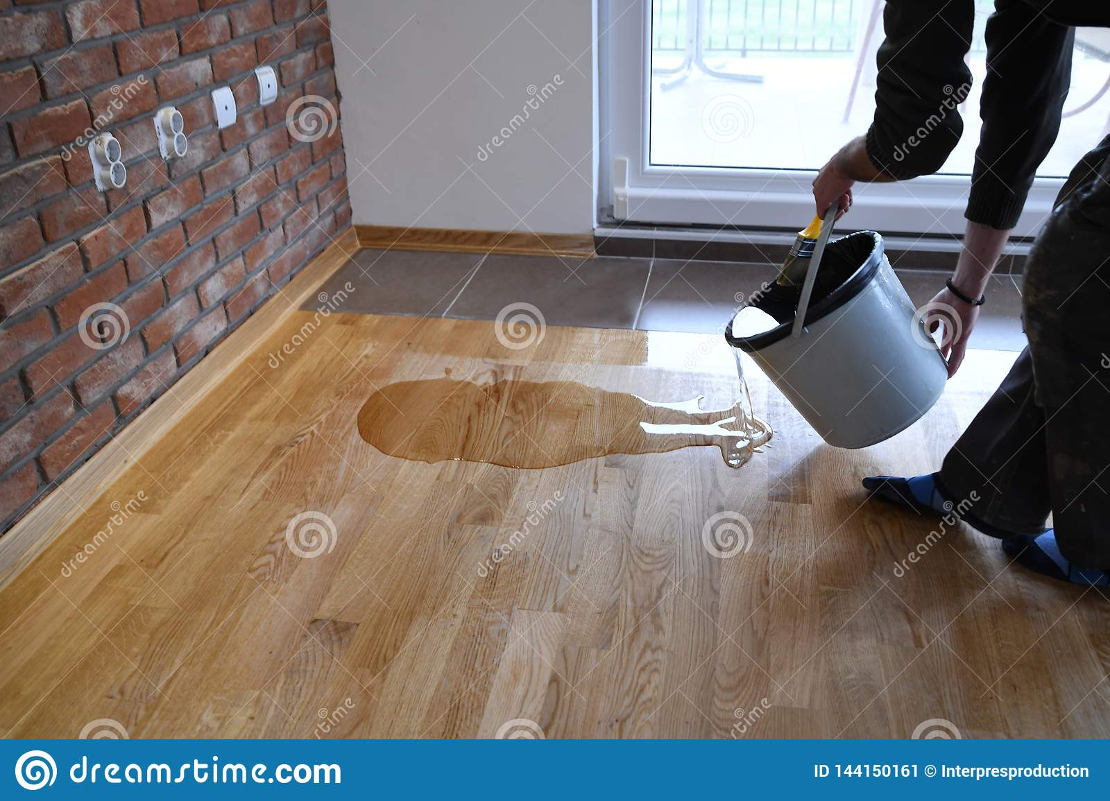 Worker Pouring Lacquer From The Bucket Directly Onto The Floor