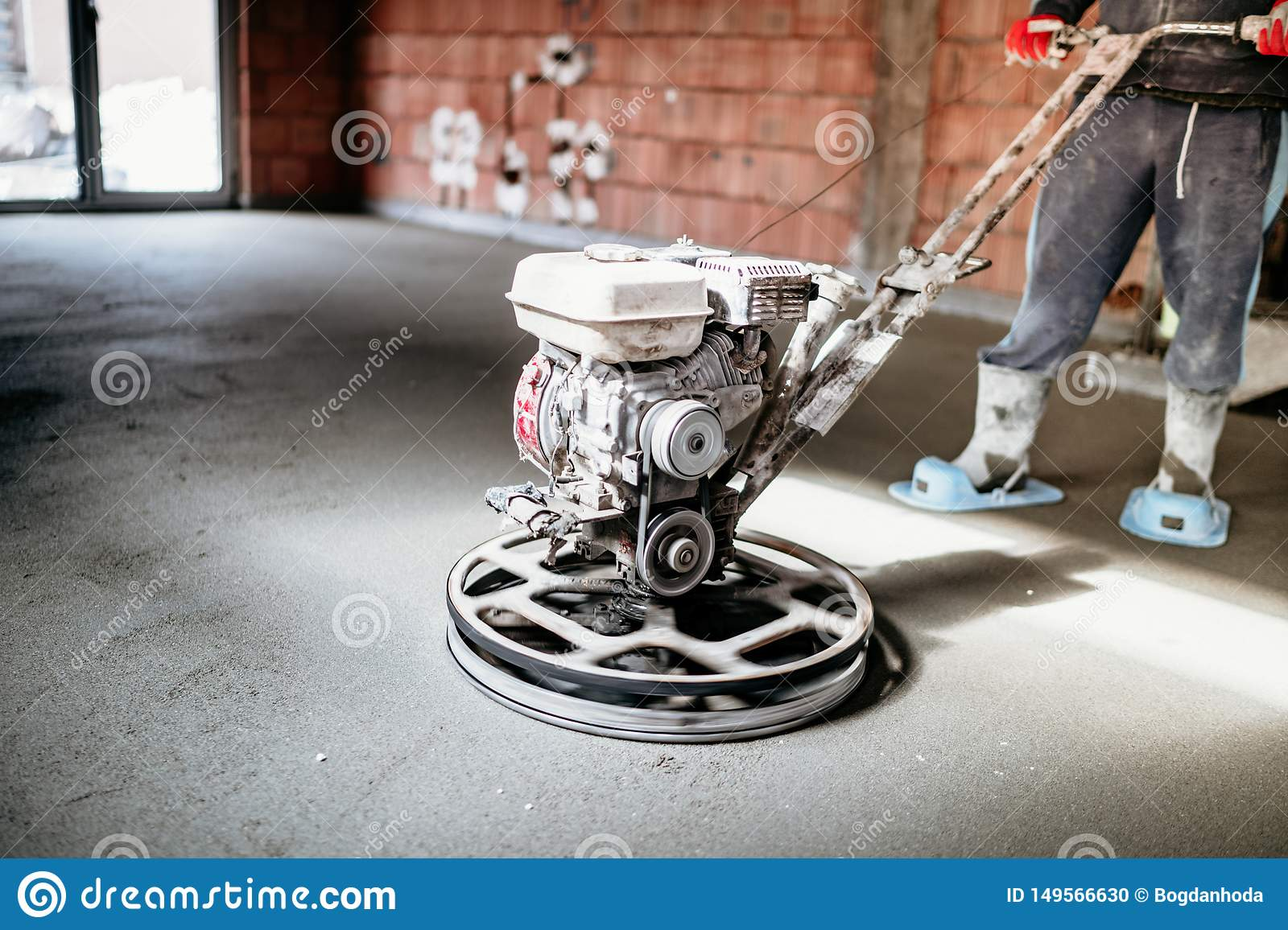 Worker With Power Trowel Tool Finishing Concrete Floor