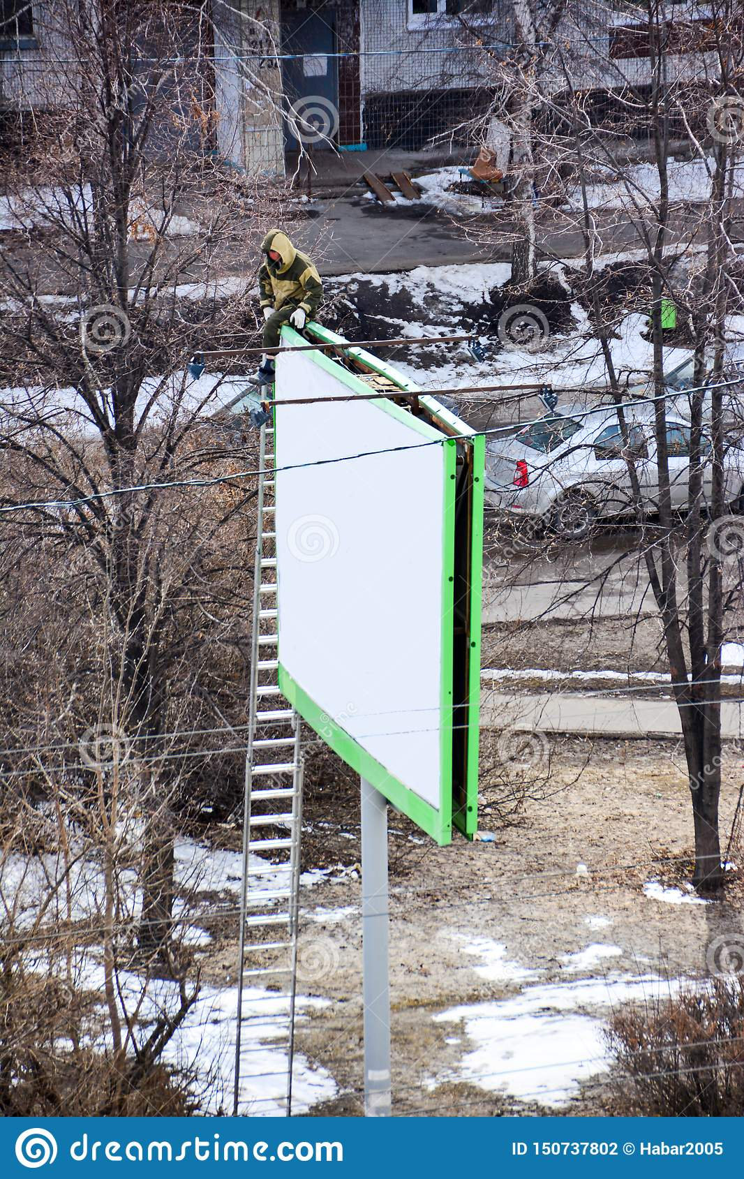 Worker prepares billboard to installing new advertisement. Industrial climber working on a ladder - placing