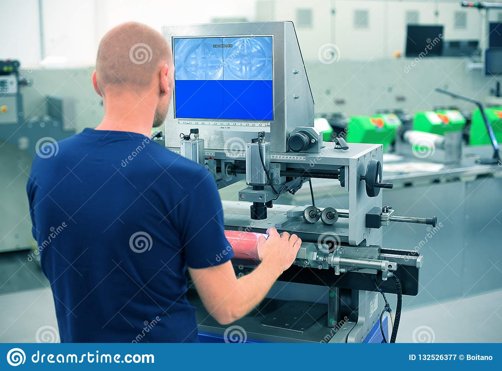 Worker in a printing and press center uses plate mounting machine to attach polymer relief plate on a printing cylinder.