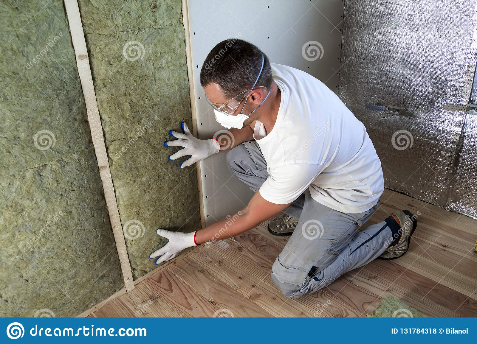 Worker in protective goggles and respirator insulating rock wool insulation in wooden frame for future house walls for cold