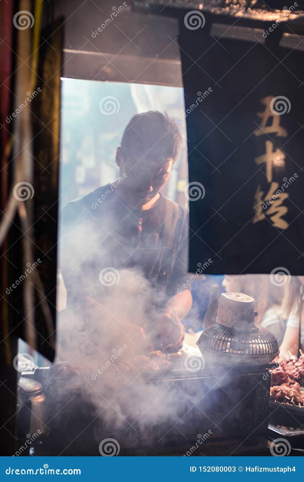 Worker of the restaurant preparing the food for the customer at traditional bar in Omoide Yokocho, Shinjuku. Portrait Orientation