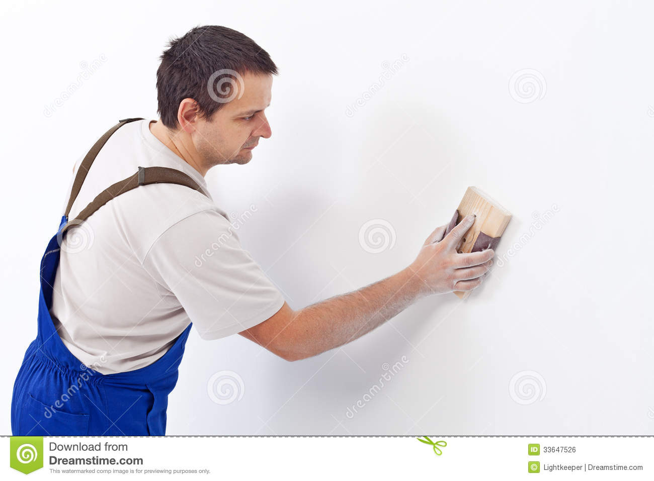 Worker scrubbing the wall with sandpaper - preparing the surface for    Worker Painting Wall