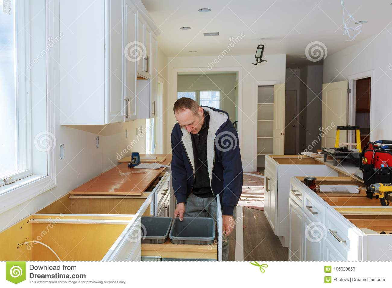 Worker Sets A On The White Cabinet With A Screwdriver ...