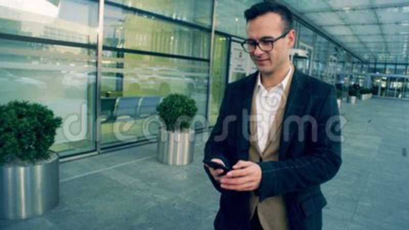 Corporate male manager walks and types on a phone, smiling, close up. A worker types on a phone while walking near business center stock video footage