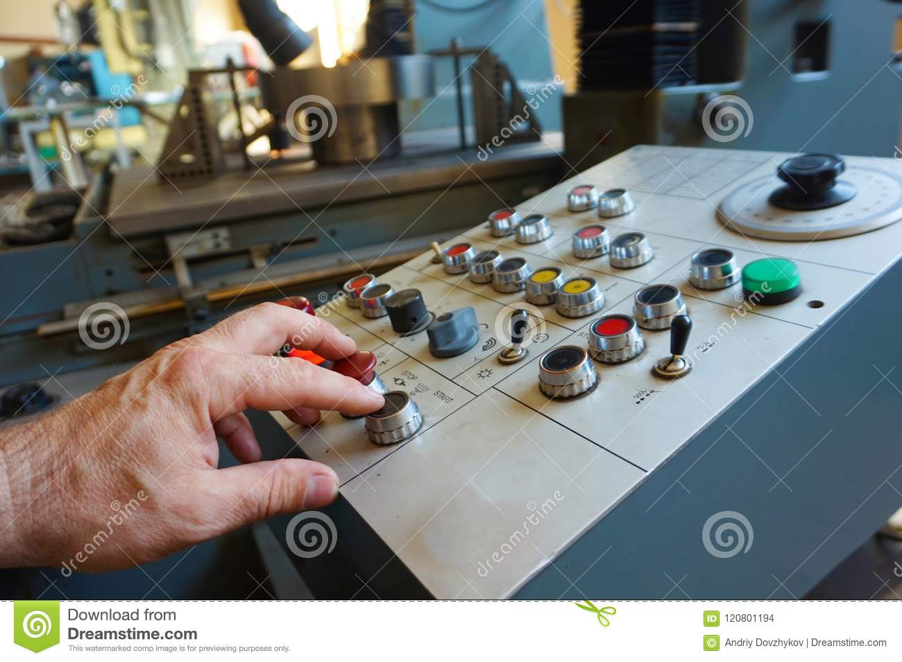 The worker uses the control panel of the CNC machine to process the material.