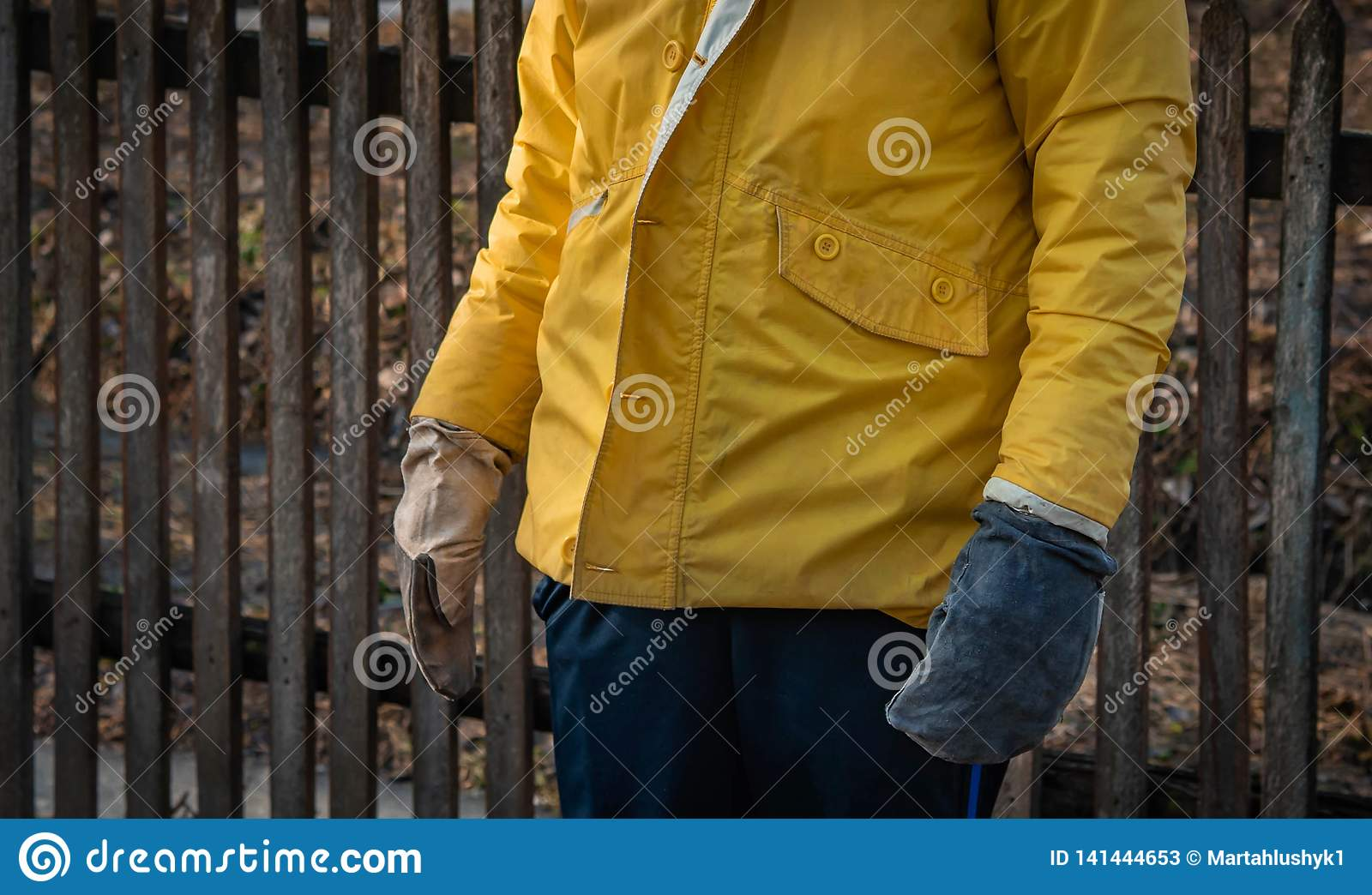 The worker is in working gloves and a working jacket