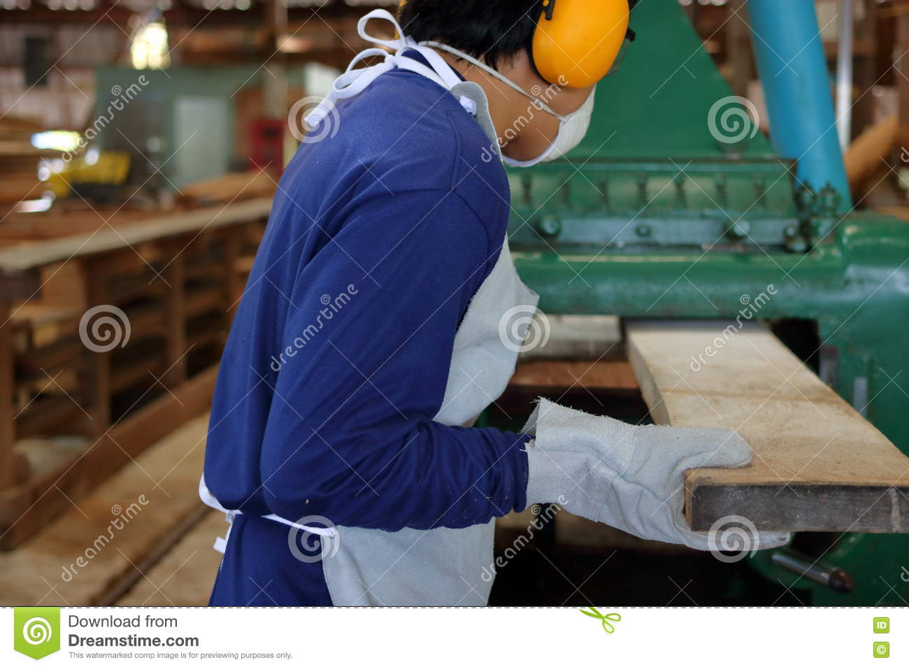 Worker is working with planing of wood machine.He is wearing safety equipment in factory. Rear view