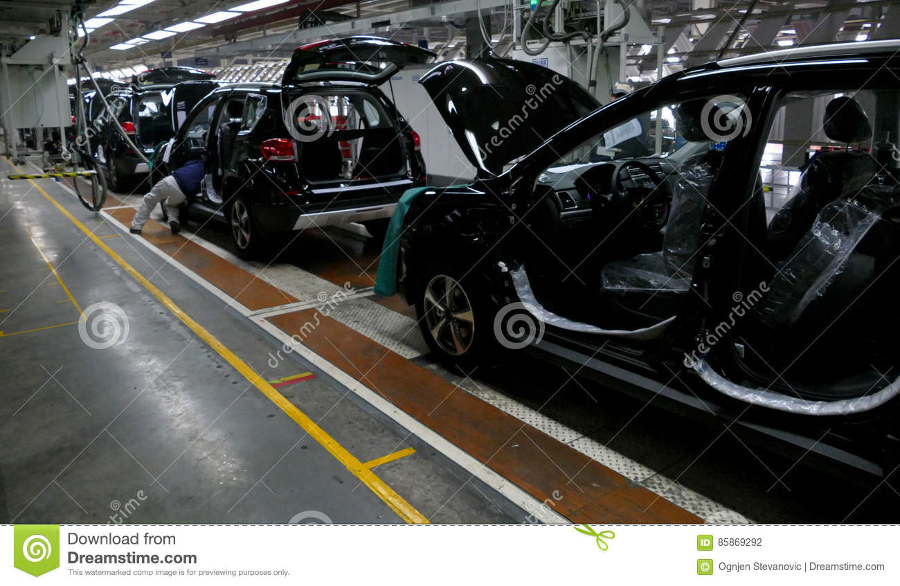 Workers assemble a car on assembly line in car factory