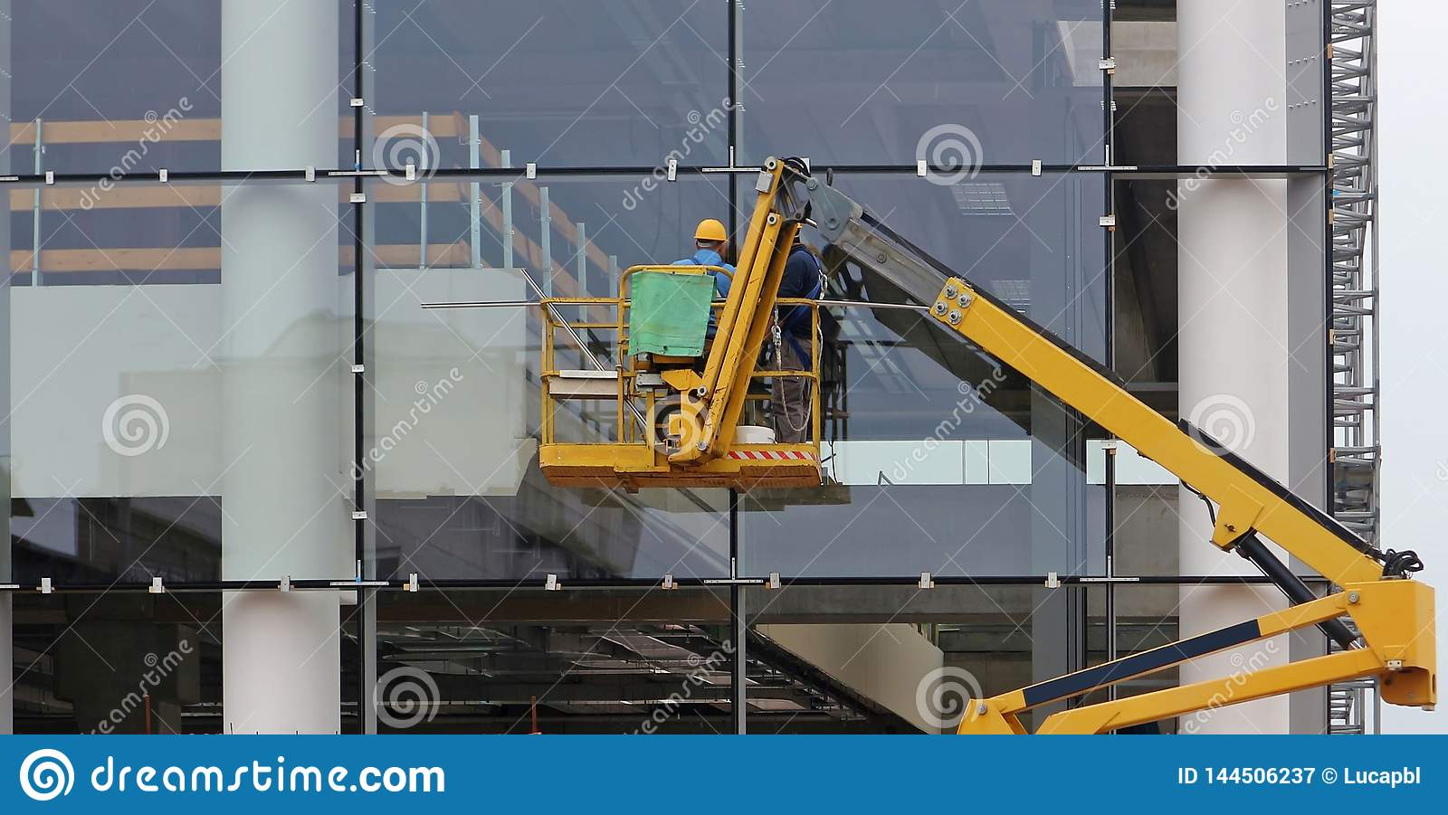 Workers on a cherry picker. They are finishing the glass facade of a building under renovation