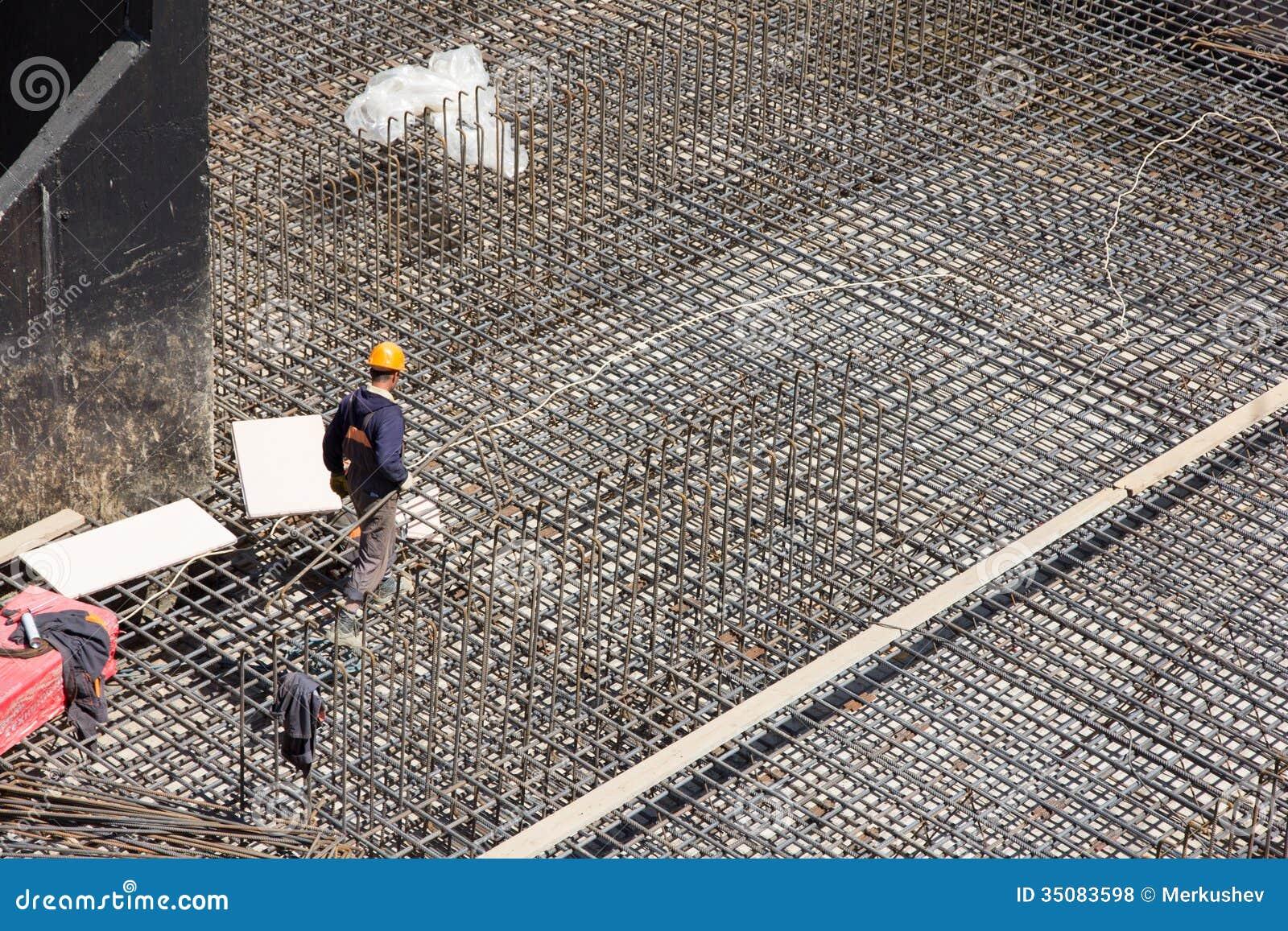 Precast Concrete Curb Reinforcement : Workers make reinforcement for concrete foundation stock