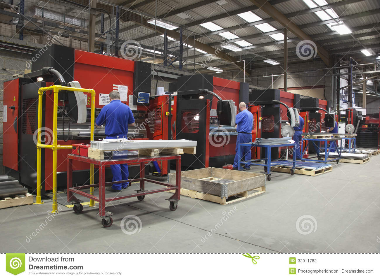 Workers At Manufacture Workshop Operating Machines