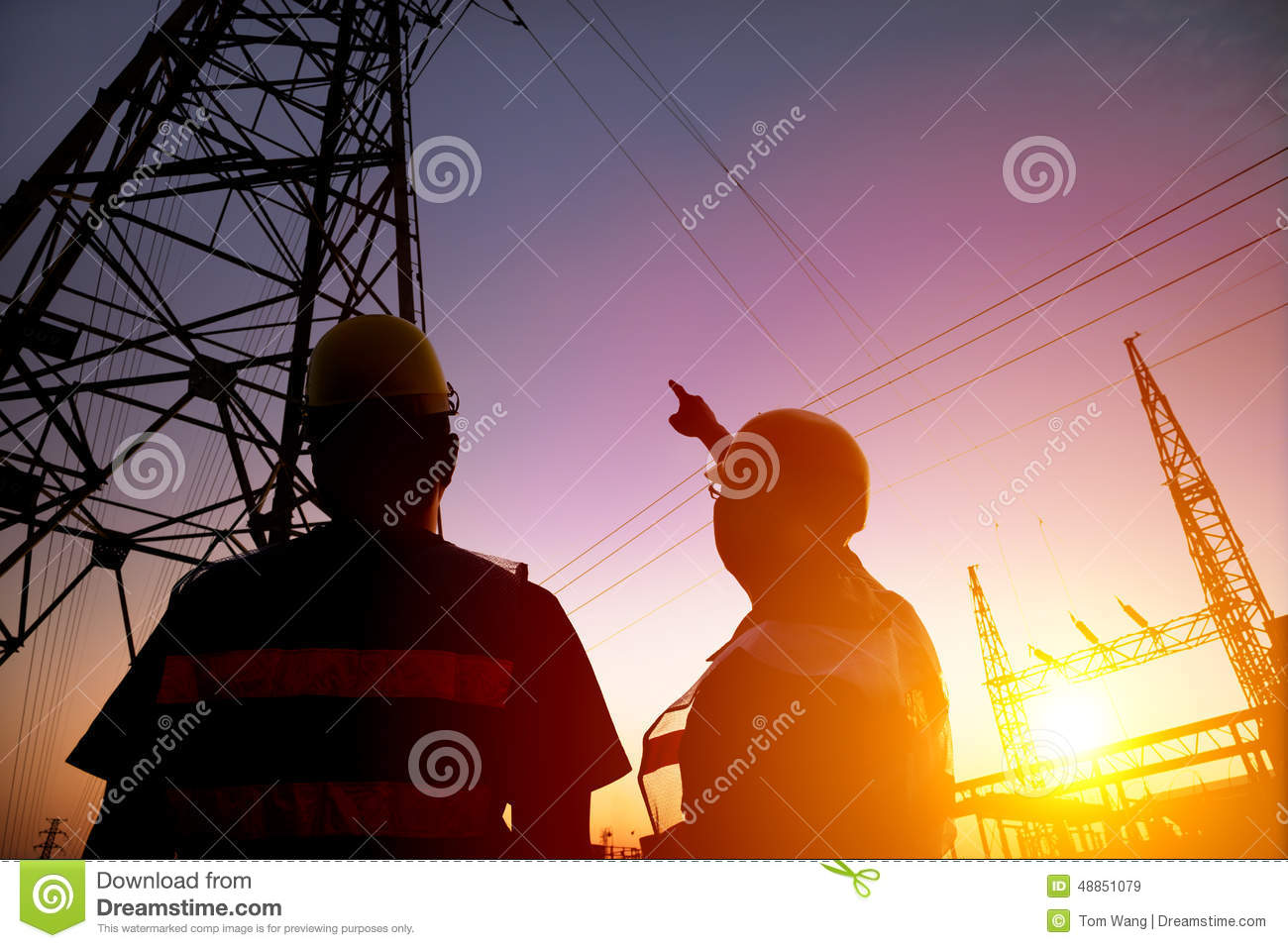 workers watching the power tower and substation with sunset b