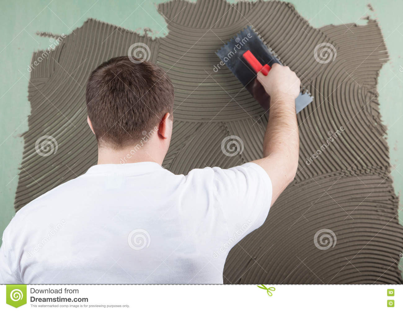 Working With Ceramic Tile : Working builder applies glue on a wall for ceramic tile