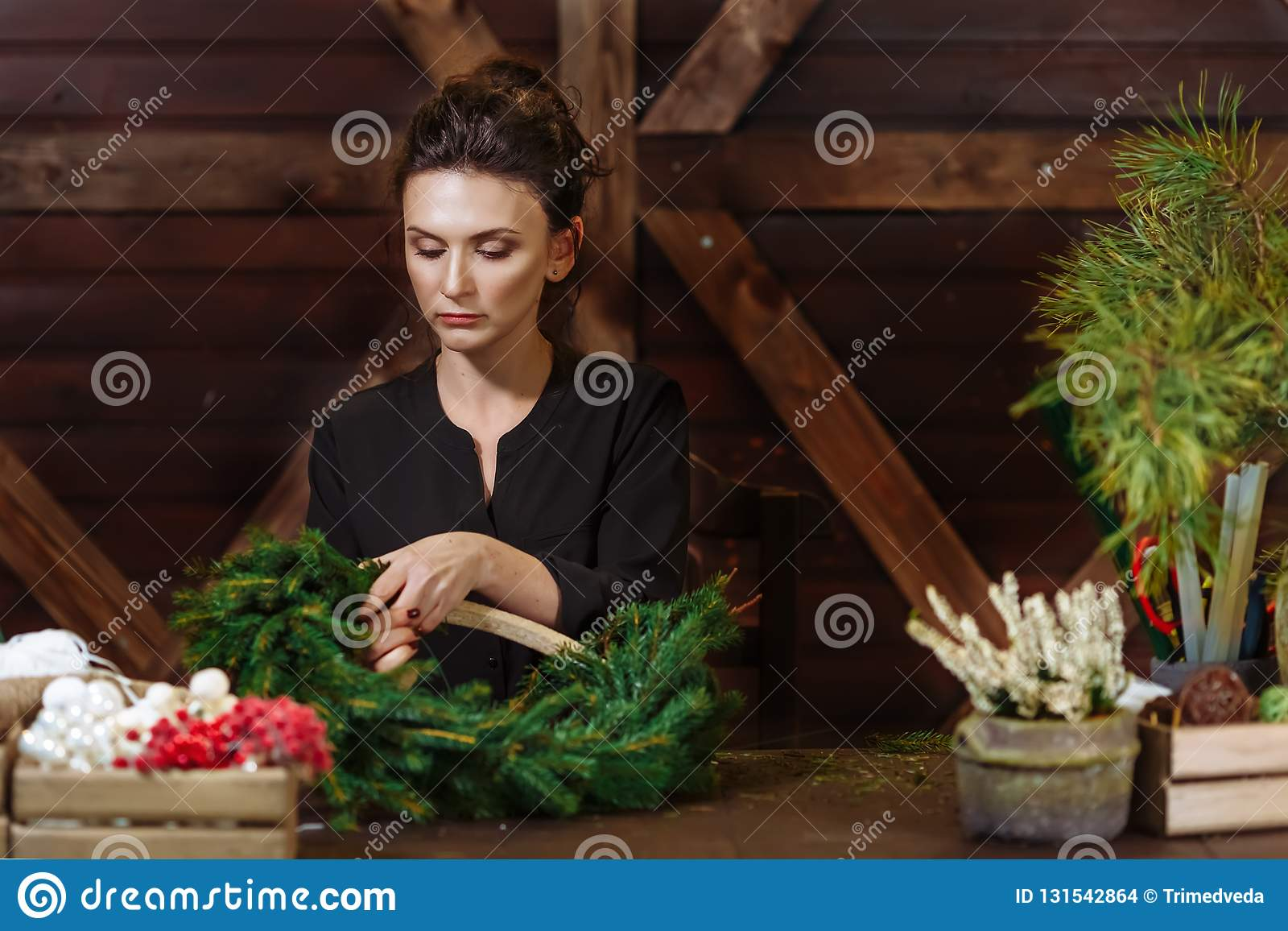 Working Florist Woman with Christmas Wreath. Young Cute smiling Woman designer preparing Christmas Evergreen Tree Wreath