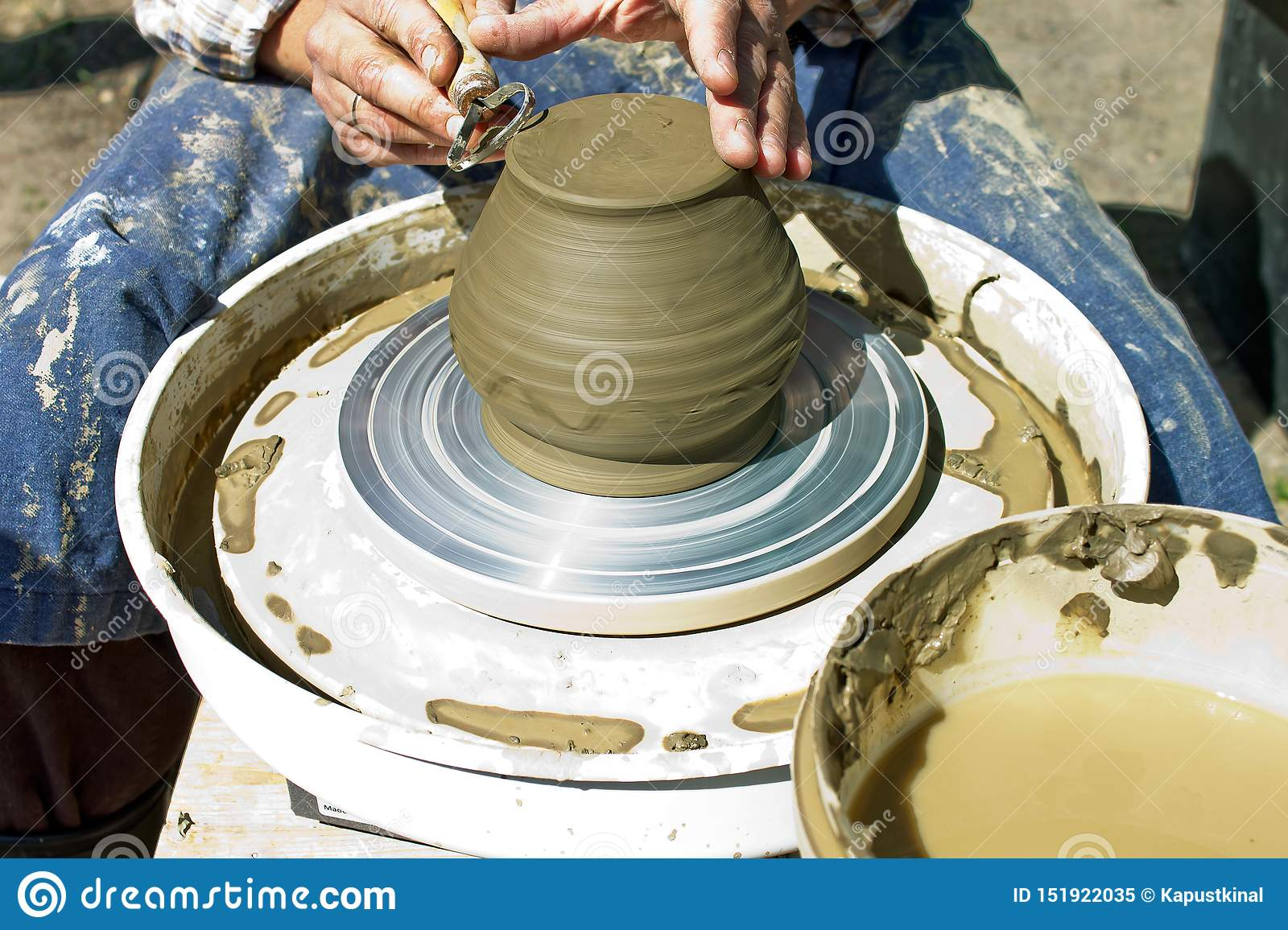 Working male hands on a potter`s wheel process a clay product in the form of a jug