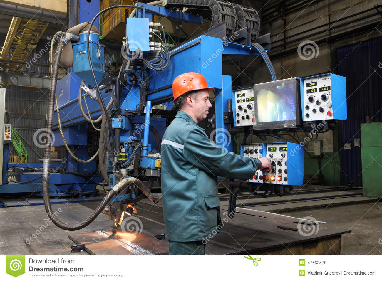 working operator controls welding robot standing at