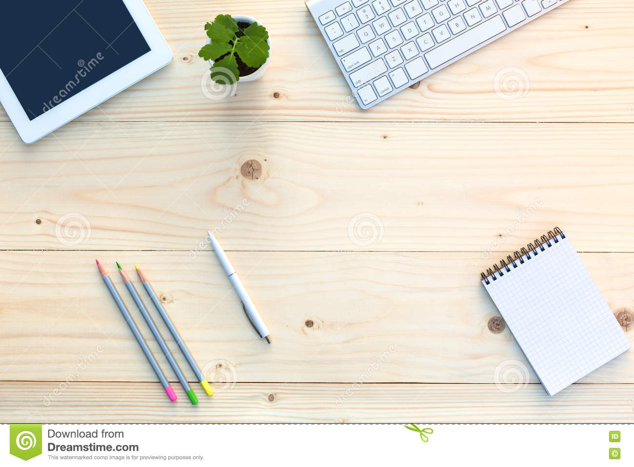 Working Place on light Wooden Desk with Stationery Electronics and Flower