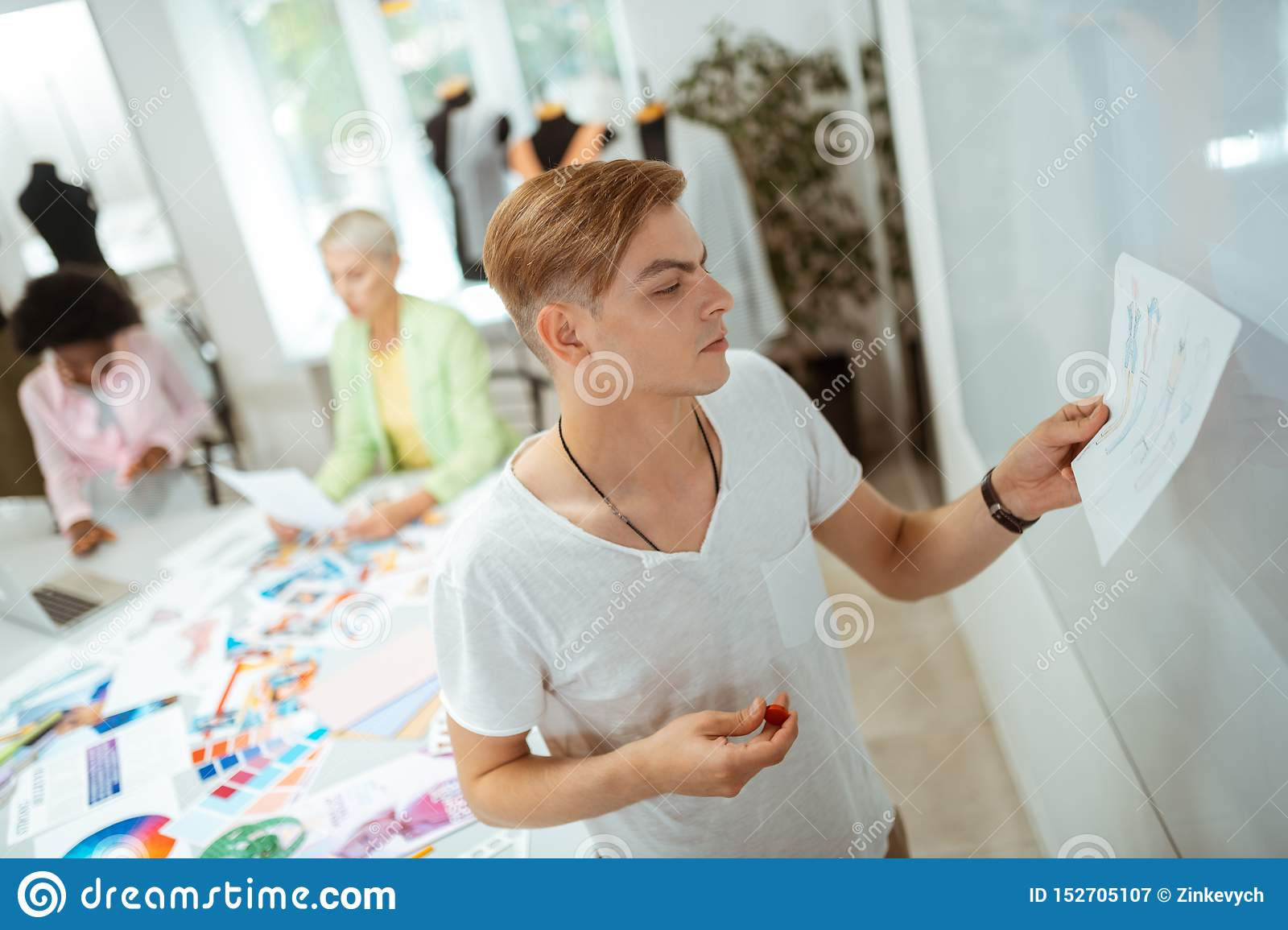 Motivated blond young man looking at his sketch