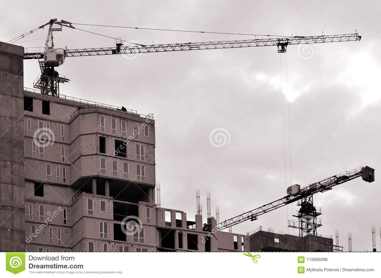 Working tall cranes inside place for with tall buildings under construction against a clear blue sky. Crane and building working