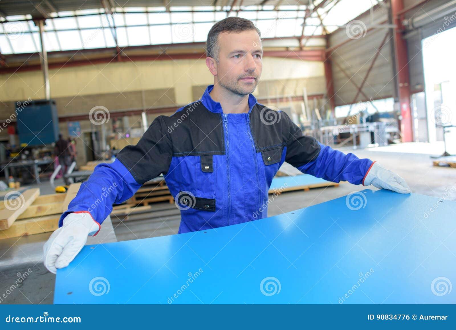 Workman holding sheet metal
