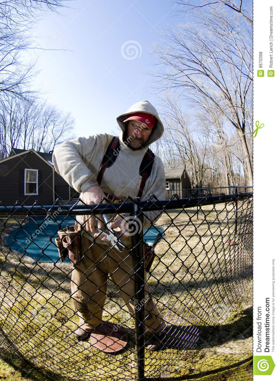 Workman repairing building chain link fence stock