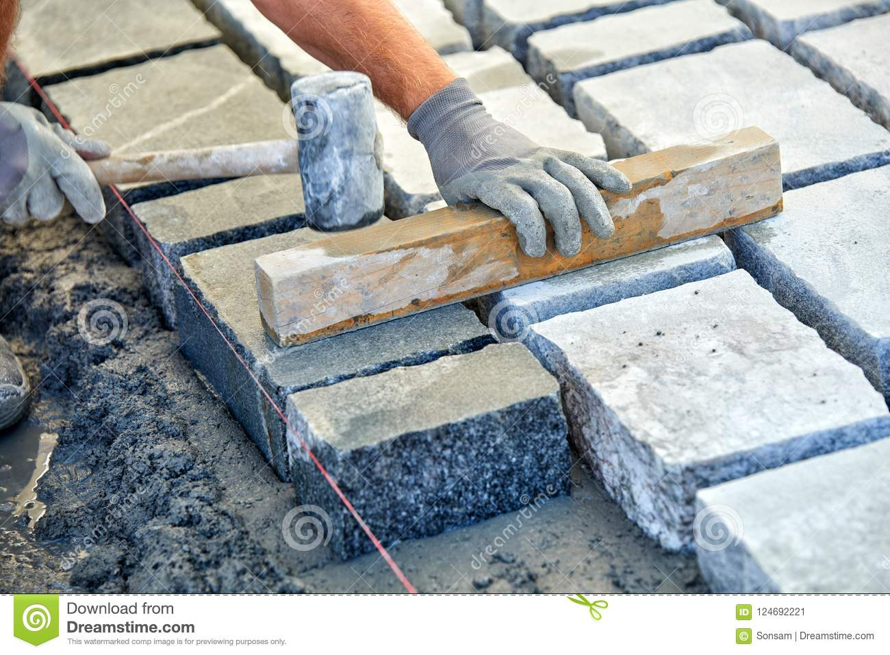 A Workman`s Gloved Hands Use A Hammer To Place Stone Pavers