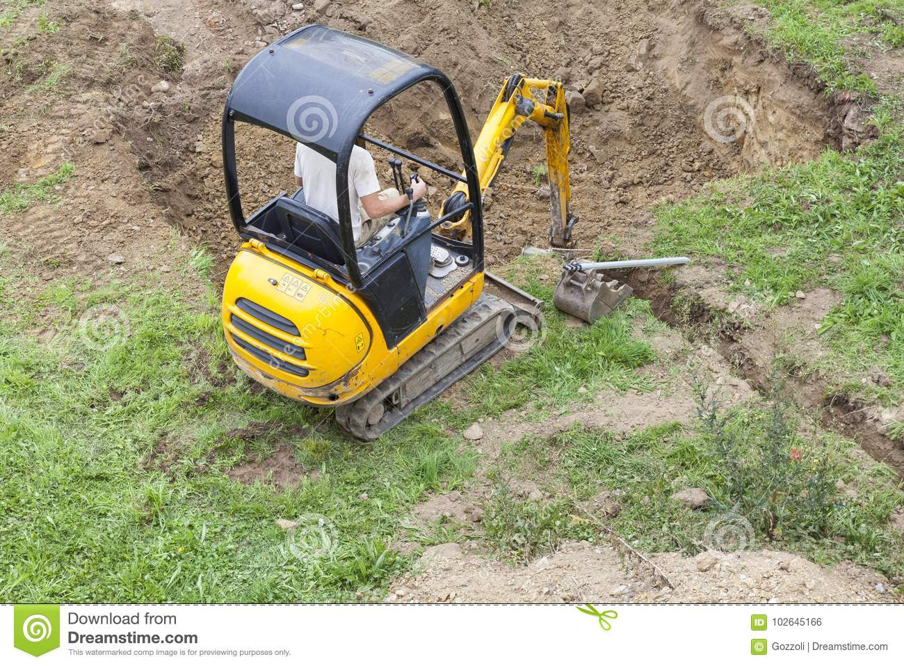 Workman using a mini digger to dig a hole for a swimming pool