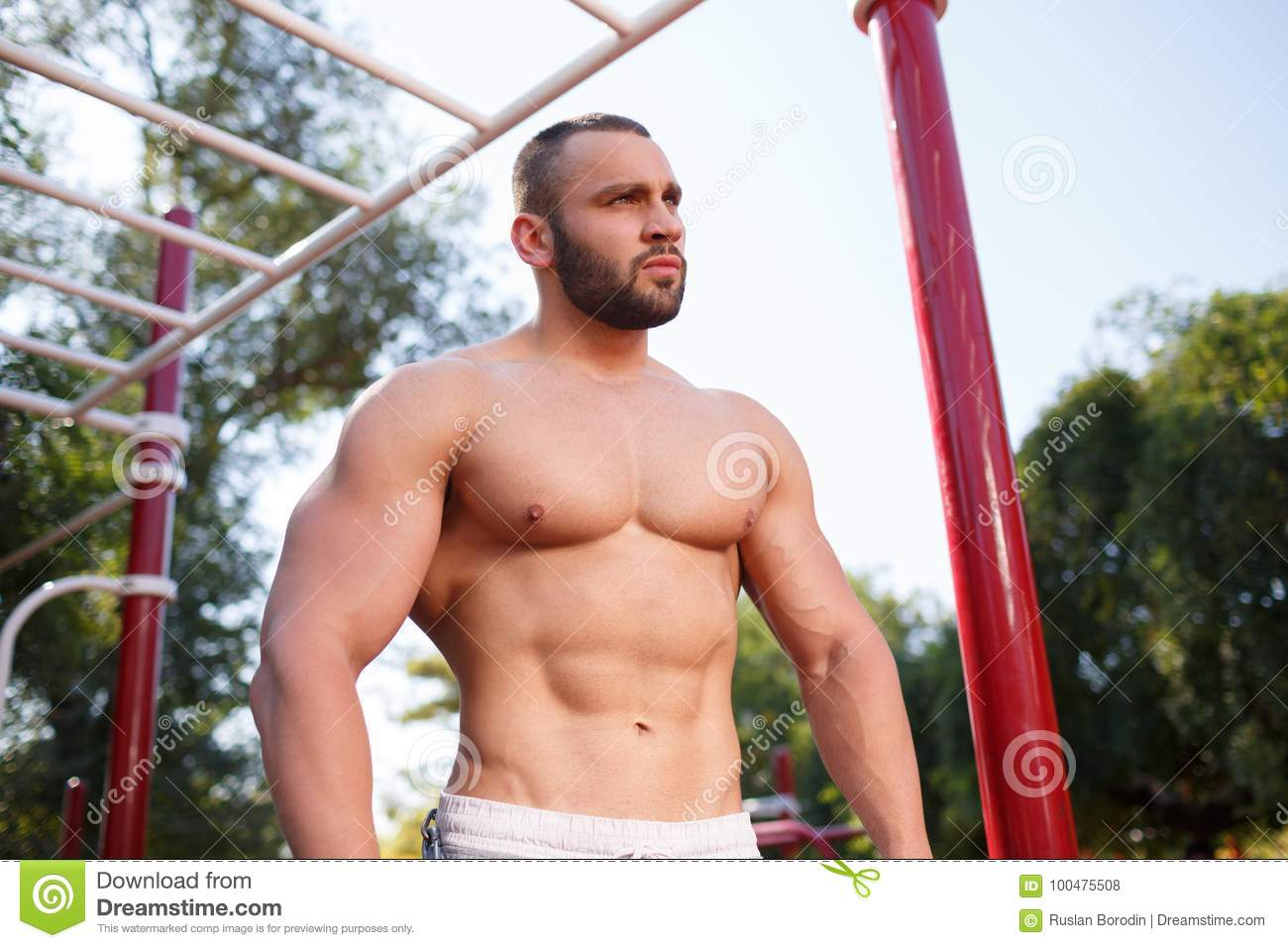 Muscular Man Stands Near The Counter With Dumbbells In The