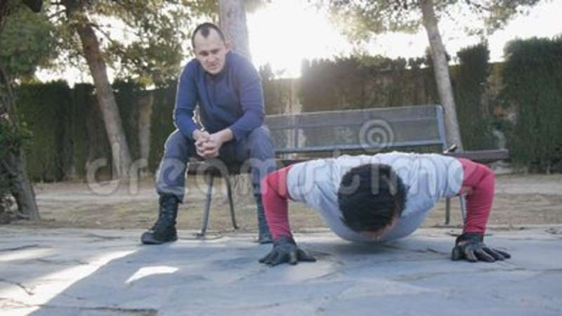 Workout with personal trainer outdoors  Male athlete doing super slow  push-ups in a park as part of a workout routine