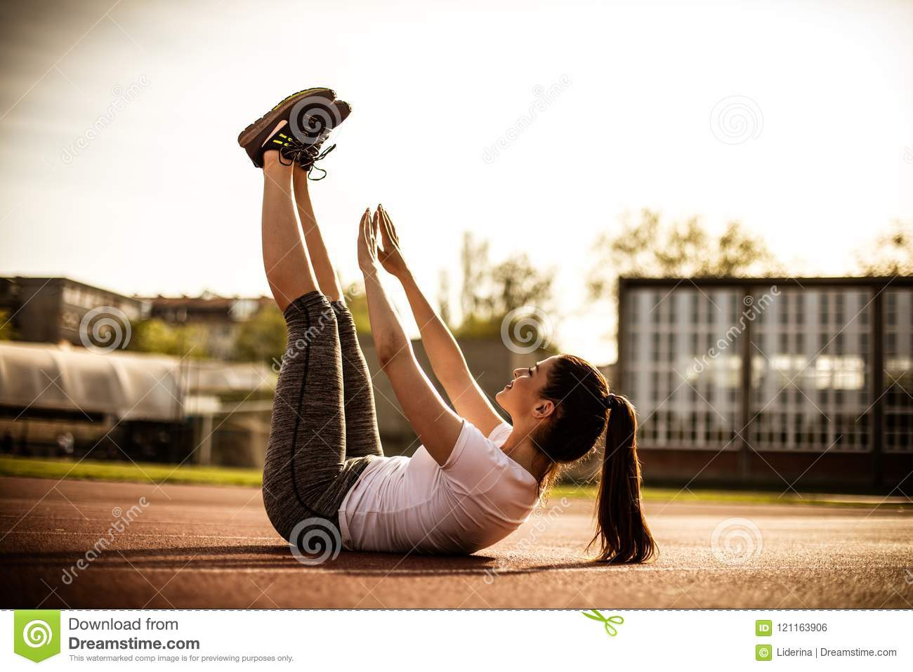 Female Athlete Stretches Legs And Body After Outdoor