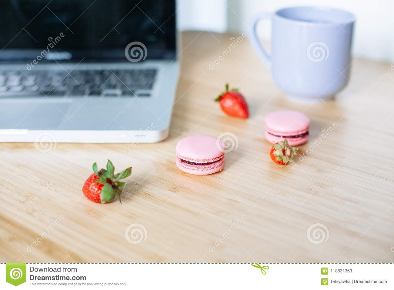 Workplace with laptop, macaroons, strawberry and cup of tea