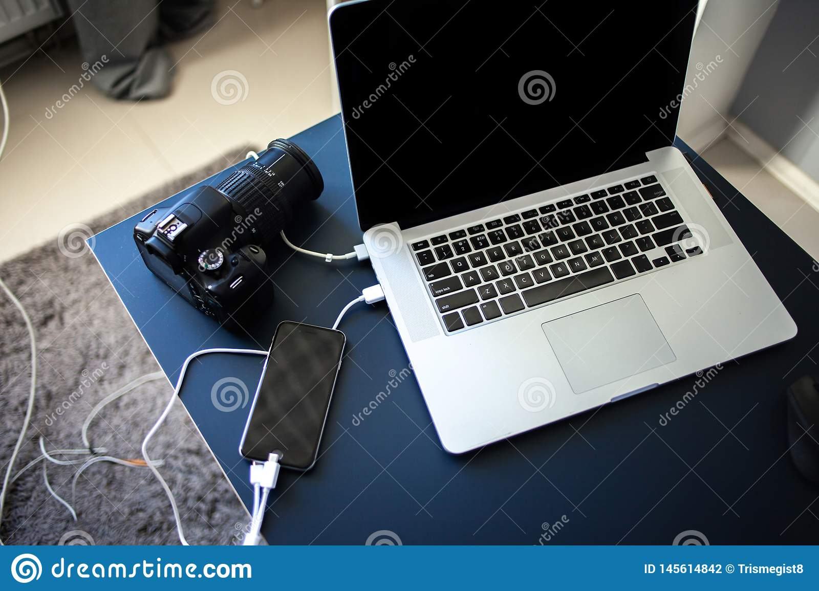 Workplace photographer and designer, laptop with camera and smartphone on the table.