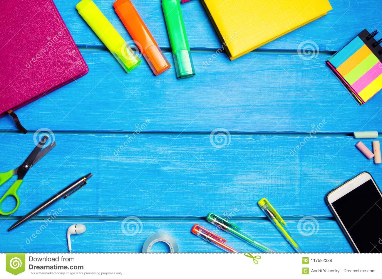 Workplace of the pupil of the school on a blue wooden table. Creative disorder, scattered pens and pencils. Place for text, nobody