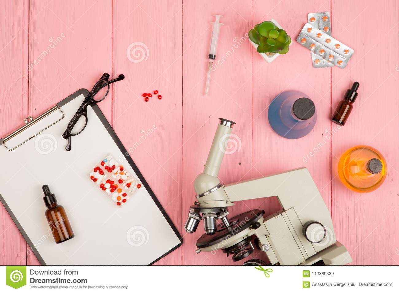 Workplace scientist doctor - microscope, pills, syringe, eyeglasses, chemical flasks with liquid, clipboard on pink wooden table