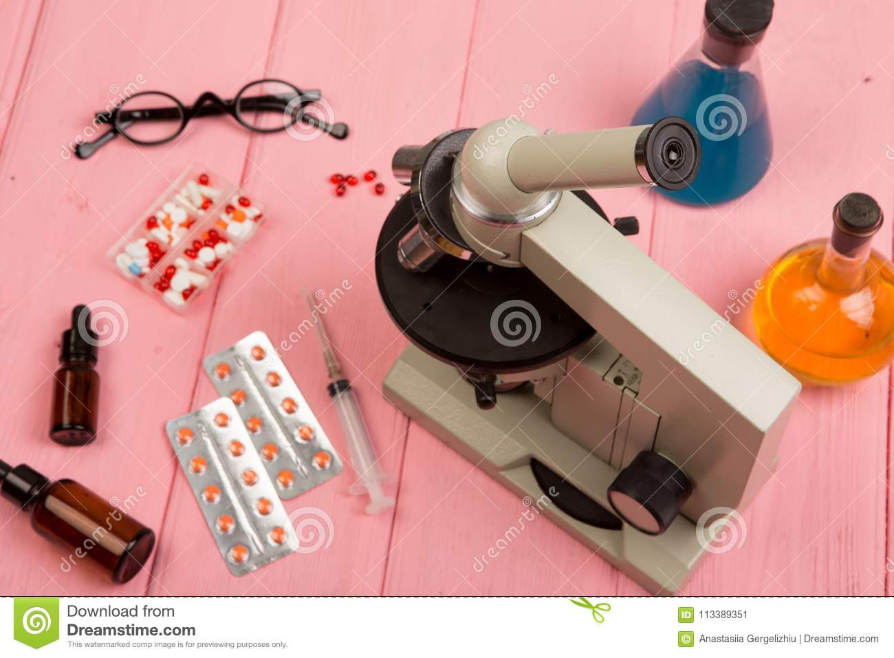 Workplace scientist doctor - microscope, pills, syringe, eyeglasses, chemical flasks with liquid on pink wooden table