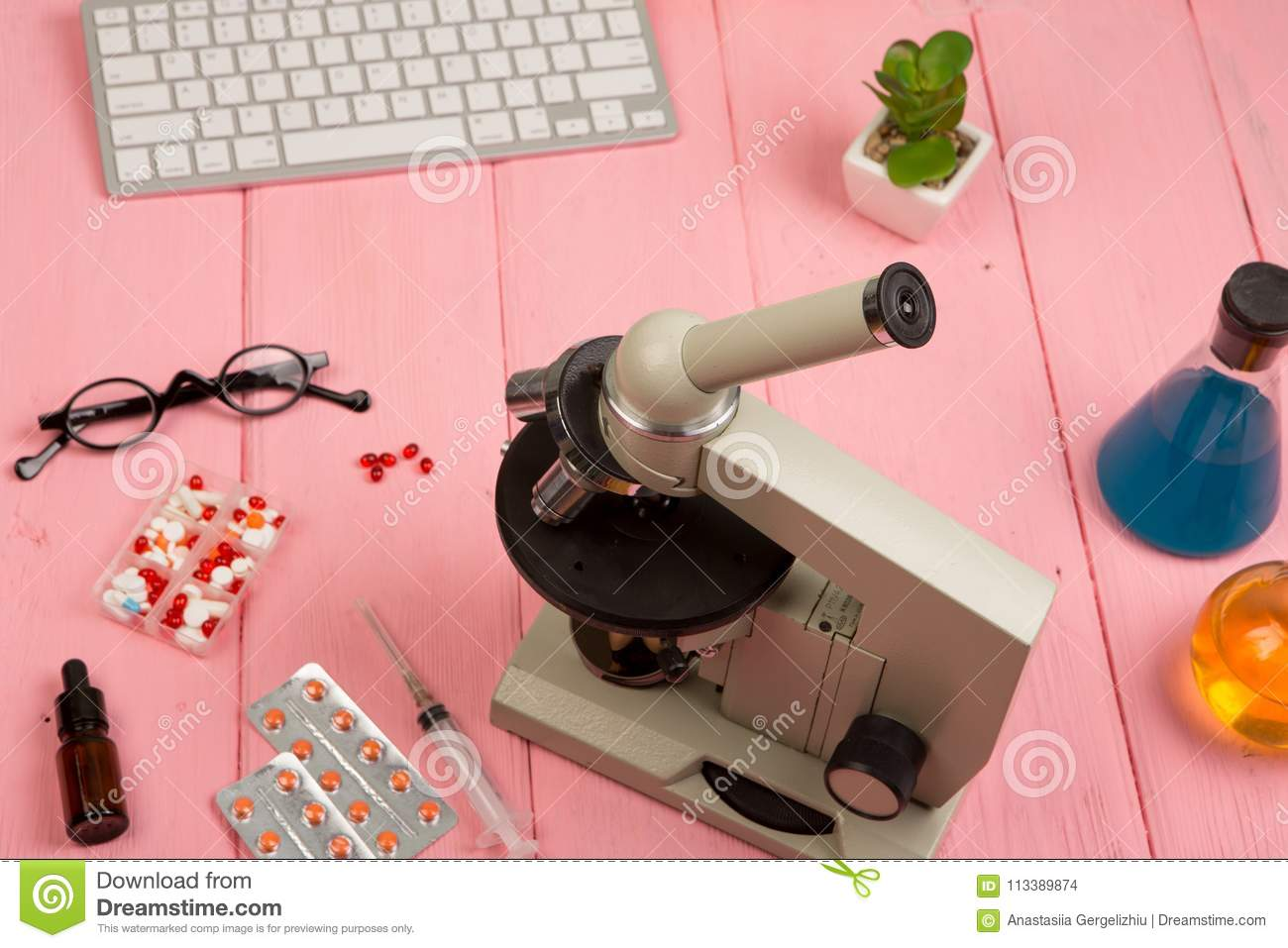 Workplace scientist / doctor - microscope, pills, syringe, eyeglasses, chemical flasks with liquid on pink wooden table