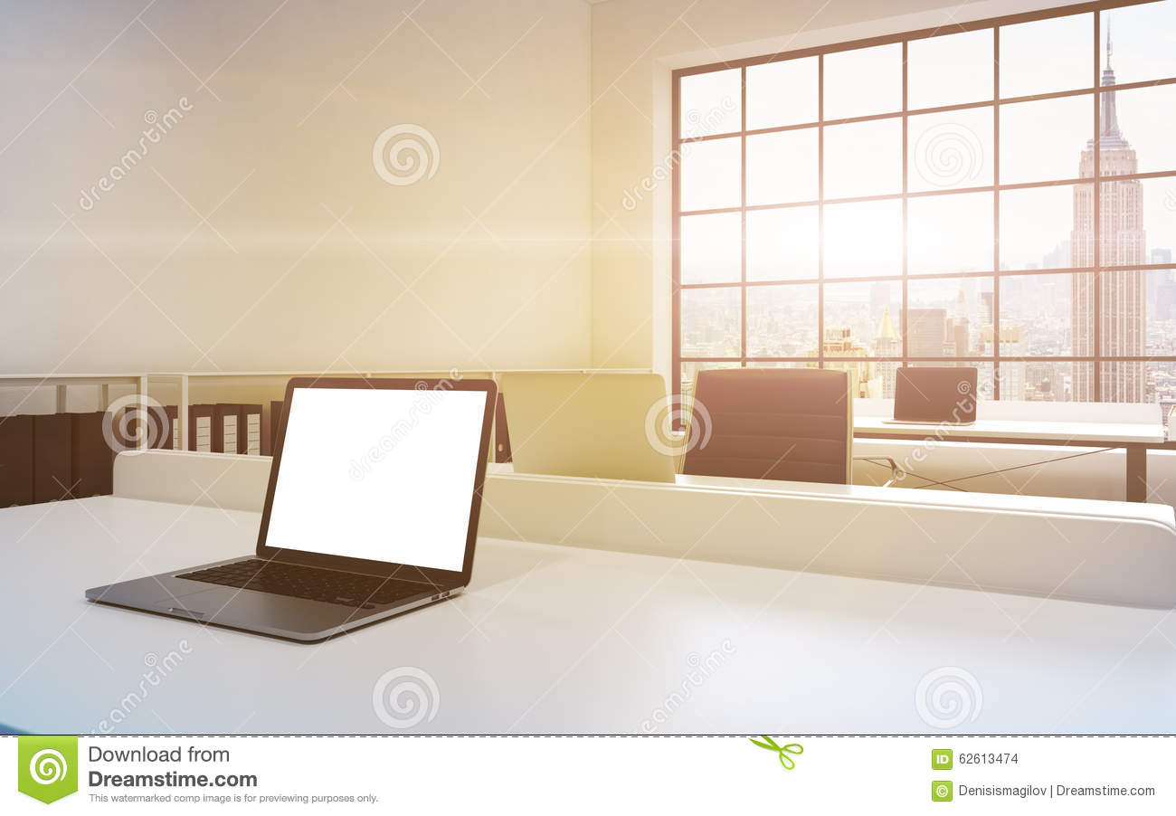Workplaces in a bright modern loft open space office. Tables equipped with laptops, white copy space in the screen. Docs shelves.