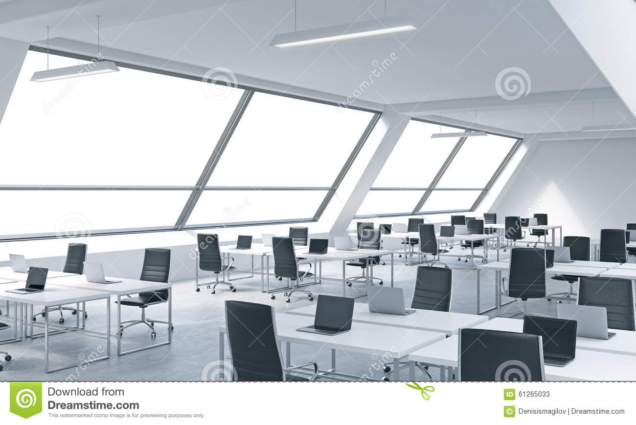 workplaces in a bright modern open space loft office white tables equipped by modern laptops bright modern office space