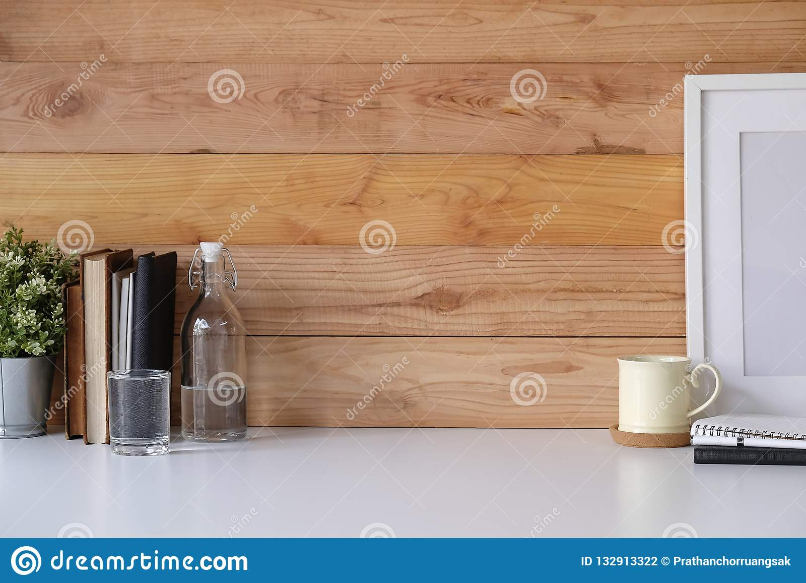 Workspace with copy space coffee mug, plant, photo frame, glass