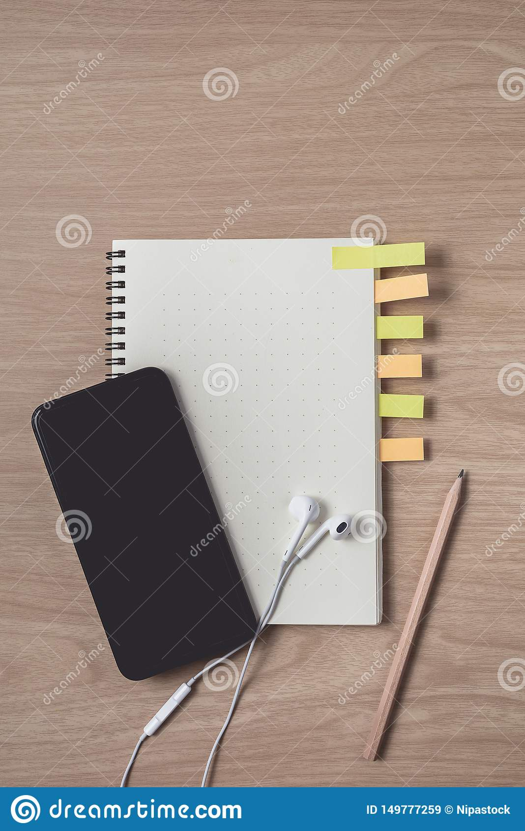 Workspace with diary or notebook and smart phone, Earphone, pencil, sticky notes on wooden background