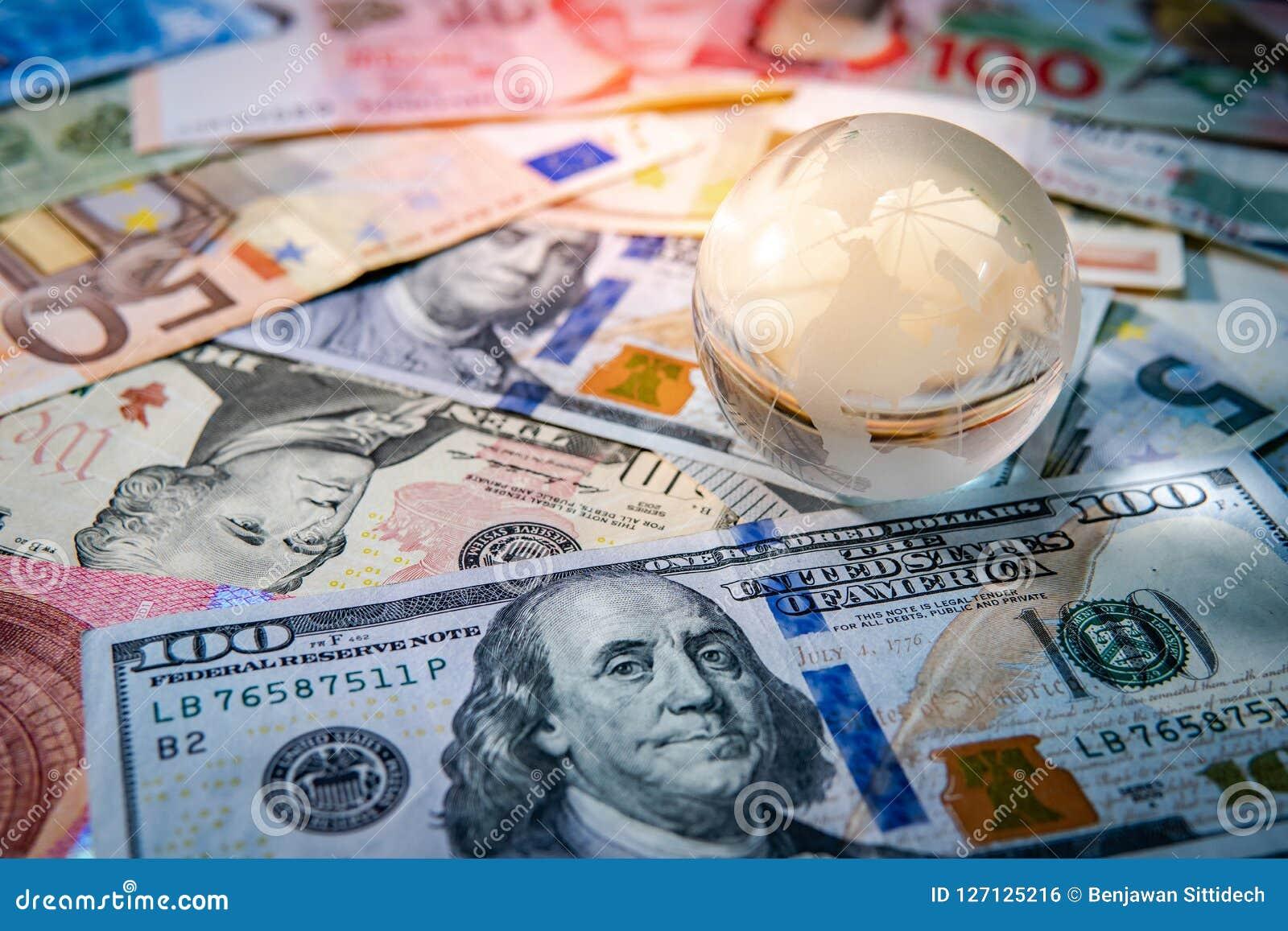 World globe crystal on various banknotes