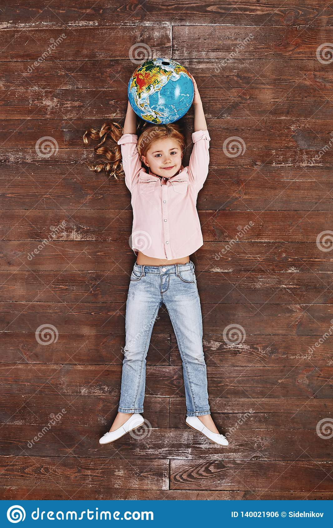 The world is mine. Girl holding globe, looking at camera and smiling