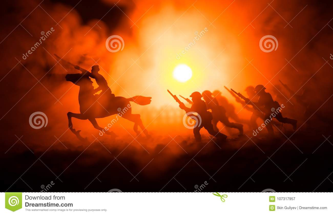 World war officer (or warrior) rider on horse with a sword ready to fight and soldiers on a dark foggy toned background. Battle sc