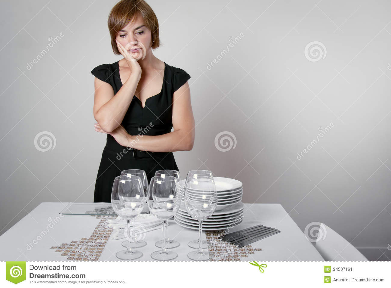 Worried woman setting the table