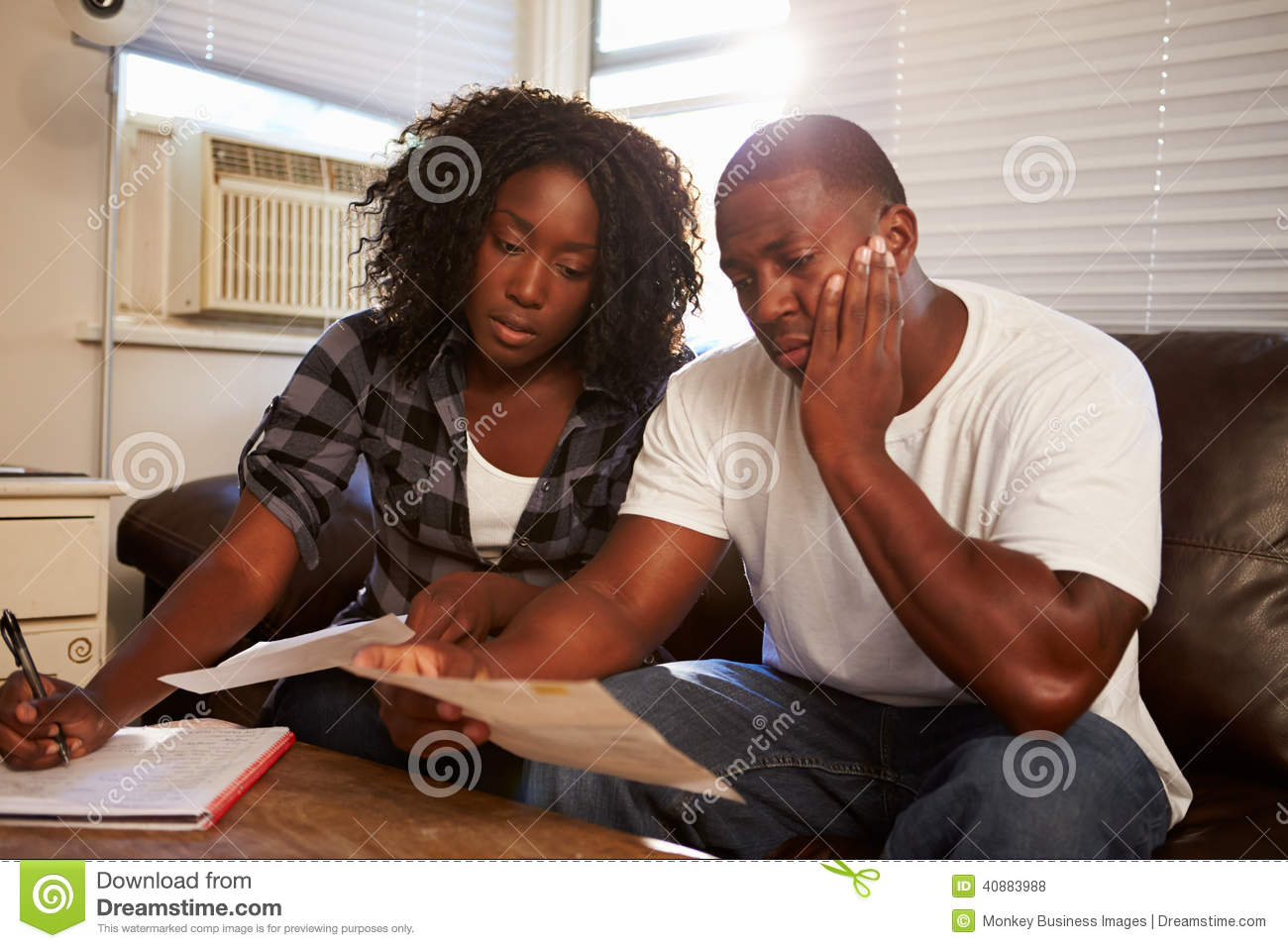 Worried Young Couple Sitting On Sofa Looking At Bills