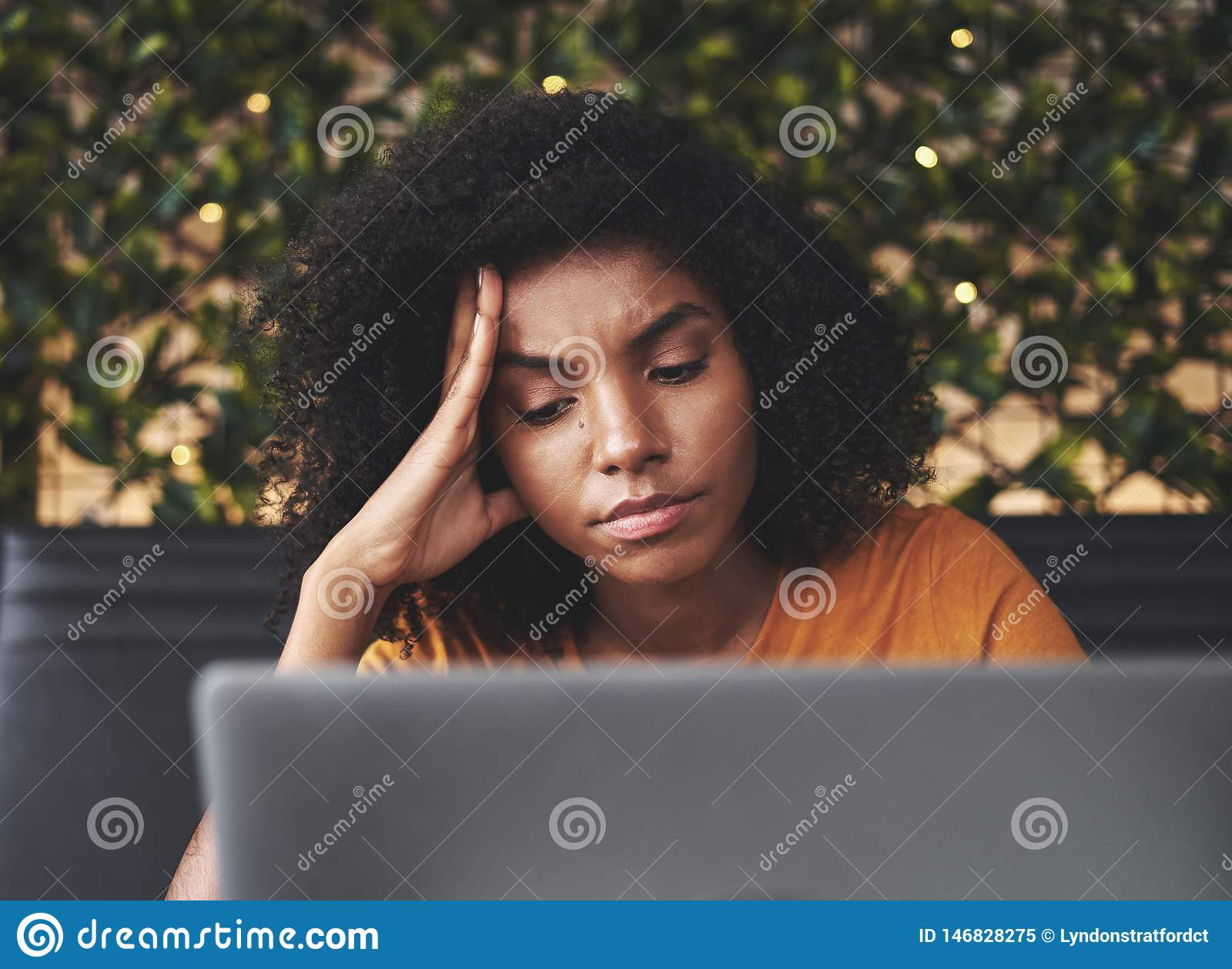 Worried young woman looking at laptop in cafe