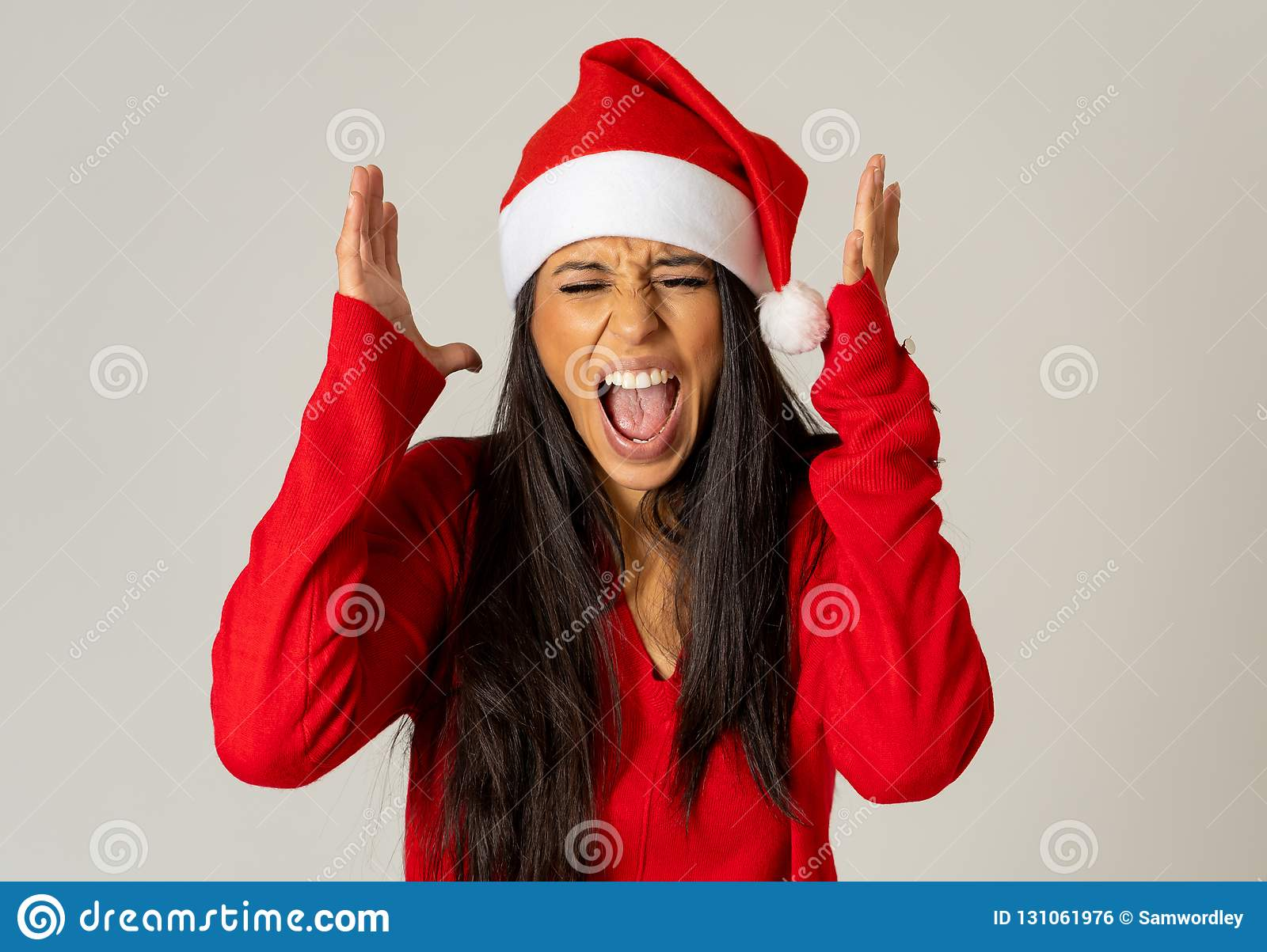 Worried young woman in santa clause hat screaming in stress running out of time for christmas