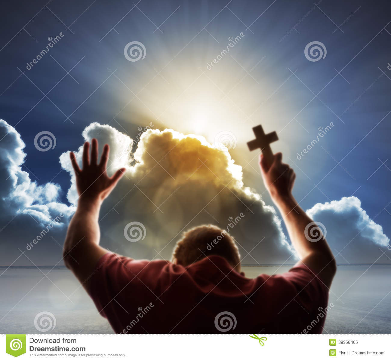 Praying man lifts his hands in prayer and holds a cross to heaven with ...